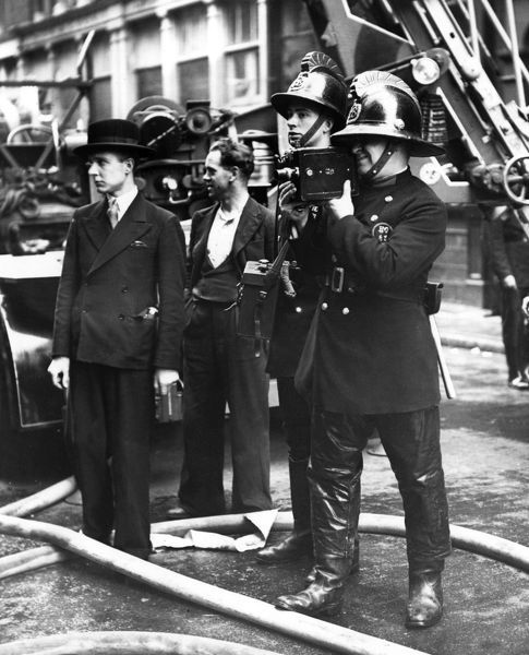 London Fire Brigade fireman-cinematographer at work, filming a fierce fire at the warehouse of Messrs Cameron and Co, Upper Thames Street, City of London, 28 June 1939