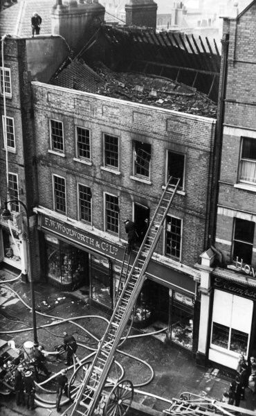 London firefighters at work outside a Woolworths building in Hampstead High Street, north-west London (11 May 1946). General aerial view of the front of the premises after the fire has been extinguished