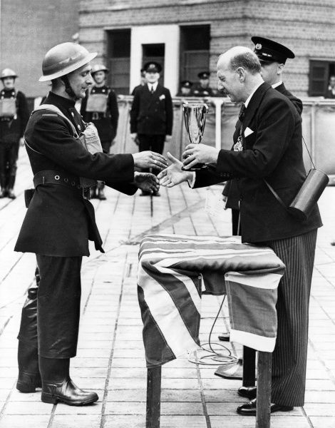 The Lord Mayor of London, Sir George Wilkinson, presenting a cup to a firefighter on 28 August 1941