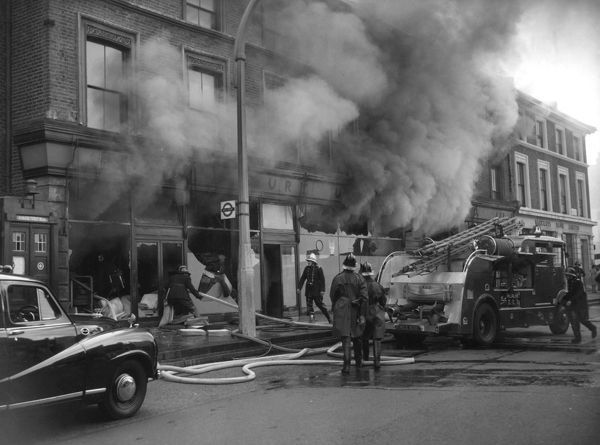 London firefighters and the London Salvage Corps (in the long coats) at the scene of a fire involving shops and dwellings in Wandsworth Road, Clapham, SW8, on 9 September 1959