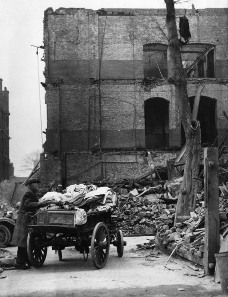 Man with a salvage cart full of bundles of material, near bombed-out buildings in London during the Second World War