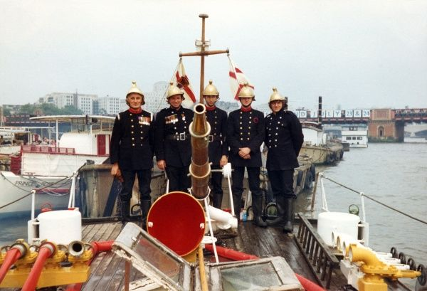 The London Fire Brigade's Massey Shaw fireboat with five firefighters on deck behind the hose, two of them with medals on their uniforms