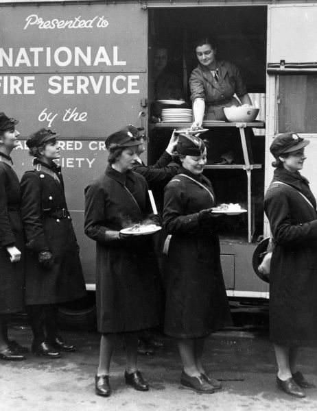 An NFS (London Region No 5) mobile kitchen in operation, handing out meals to women in uniform. The vehicle was donated by the Canadian Red Cross