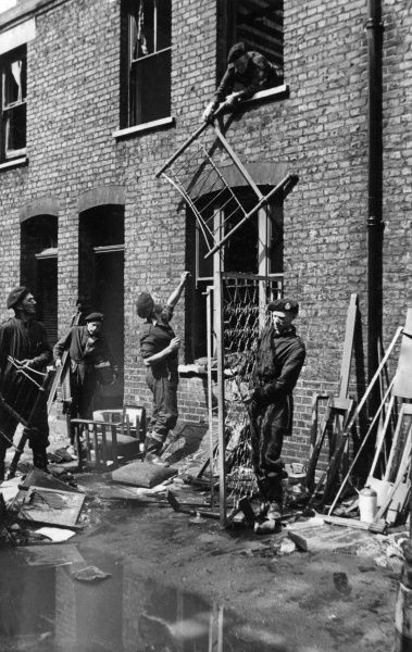 NFS overseas personnel in a salvage operation, helping to remove furniture from damaged houses, 27 June 1944