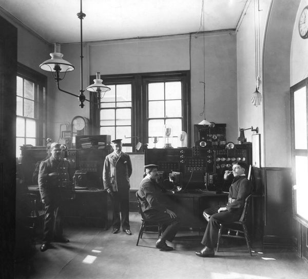 Watchroom at Metropolitan Fire Brigade headquarters in Southwark Bridge Road, with men manning the switchboard and monitoring the fire alarm control board where calls for assistance were received