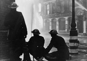 Firefighters tackle a blaze caused by a bombing raid.