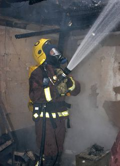 Firefighter in breathing apparatus working at fire